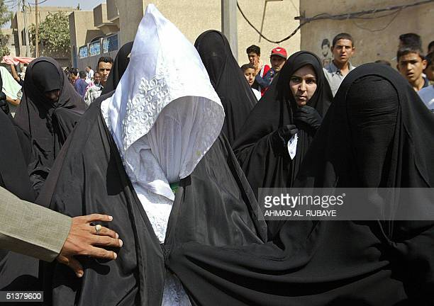 An Iraqi bride walks with her relatives during a wedding celebration at Baghdad's Shiite Sadr City neighborhood 01 October 2004 Both the bride and...