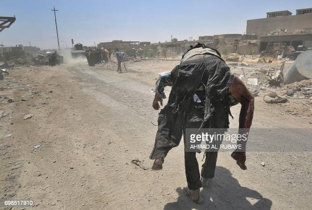 TOPSHOT An Iraqi carries a wounded man while fleeing from the Old City of Mosul as Iraqi forces advance on June 20 during the ongoing offensive to...