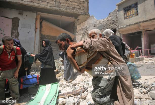 TOPSHOT An Iraqi carries and elderly man while him and others evacuate from the Old City of Mosul on June 30 as Iraqi government forces continue...