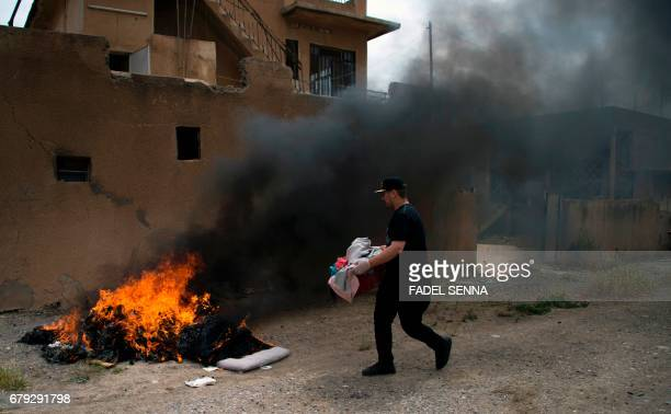 An Iraqi carries away garbage from his house to a burning fire after his return to his hometown in the predominantly Christian Iraqi town of Qaraqosh...