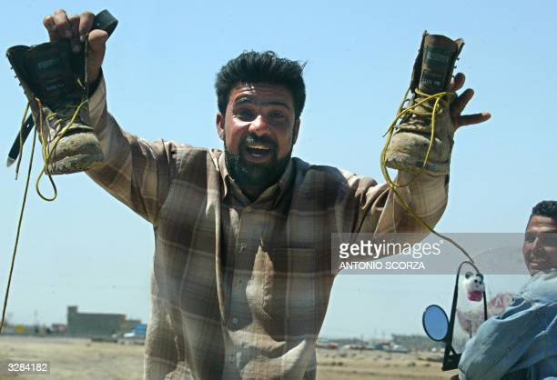 An Iraqi celebrates as he carries a pair of boots belonging to the driver of a US military tanker after insurgents attacked a US military convoy 09...