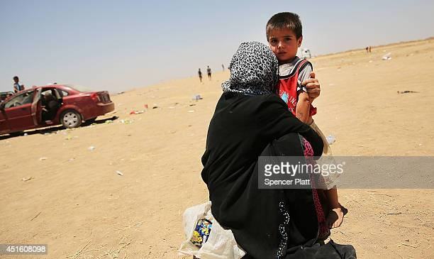 An Iraqi child and his mother wait near a camp entrance as thousands of Iraqis who have fled recent fighting in the cities of Mosul and Tal Afar try...