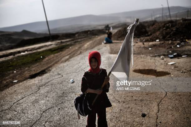 TOPSHOT An Iraqi child holding a white flag stands on a road as families flee Mosul on March 1 during an offensive by security forces to retake the...