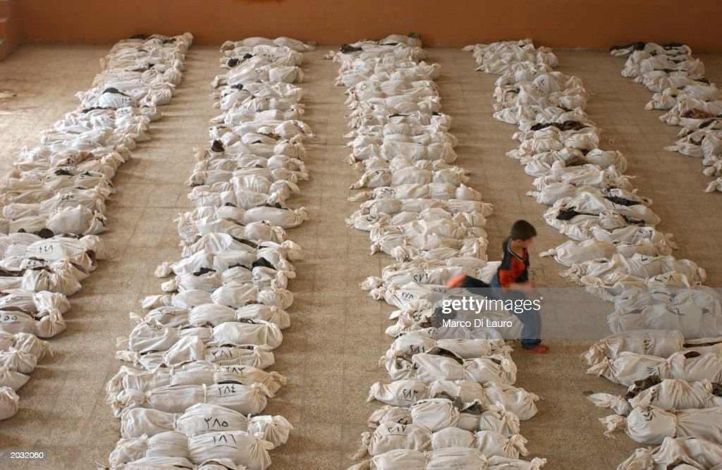 An Iraqi child jumps over a line of remains in a school where bodies have been brought from a mass grave discovered in the desert in the outskirts of Al Musayyib, 50 km south of Baghdad, May 27, 2003 in Iraq. People have been searching for days for identity cards or other clues among the skeletons to try to find the remains of family members, including children, from the grave that locals say contain the remains of hundreds of Shi'ite Muslims executed by Saddam Hussein's regime after their uprising following the 1991 Gulf War.