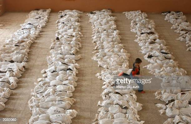 An Iraqi child jumps over a line of remains in a school where bodies have been brought from a mass grave discovered in the desert in the outskirts of...