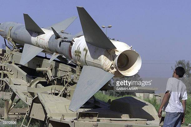 An Iraqi child looks at an Iraqi surfacetoair rocket left over from the USled war in Iraq in the western Baghdad district of Habibiya 03 August 2003...