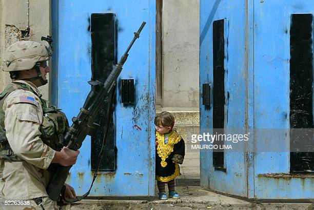 An Iraqi child peers through the front gate of her home as a US sniper soldier from the 1st Battalion 24th Infantry Regiment walks past during a...