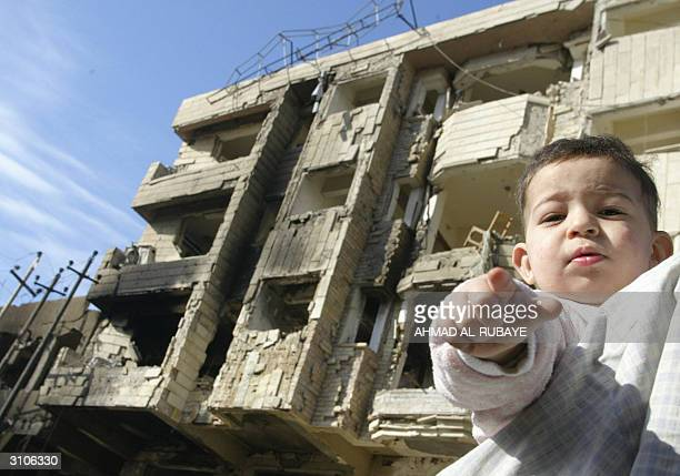 An Iraqi child points towards photographers in front of the heavily damaged Jabal Lubnan Hotel 18 March 2004 at the site of last night's powerful car...