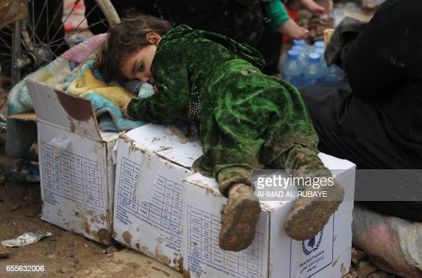 An Iraqi child rests as residents from Mosul arrive at the Hamam alAlil camp for displaced people on March 20 during the government forces ongoing...