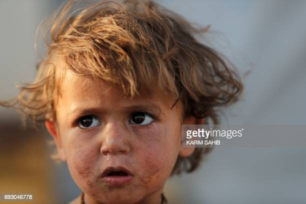 An Iraqi child stands at the AlKhazir camp for internally displaced people located between Arbil and Mosul on June 6 2017 Hundreds of thousands of...