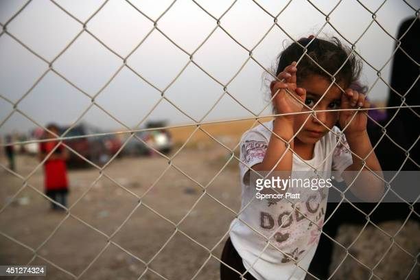 An Iraqi child waits with her family outside of a temporary displacement camp for Iraqis caughtup in the fighting in and around the city of Mosul on...