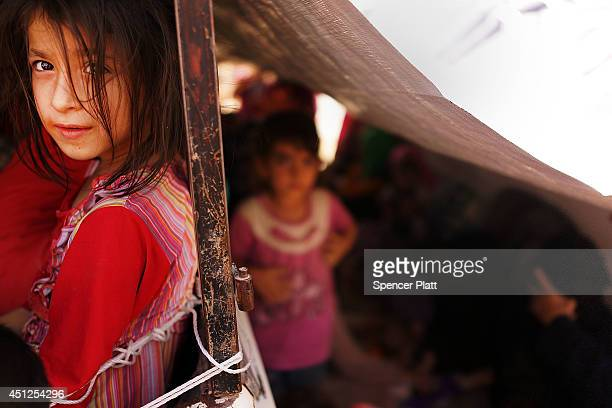 An Iraqi child waits with her family to get into a temporary displacement camp for Iraqis caughtup in the fighting in and around the city of Mosul on...