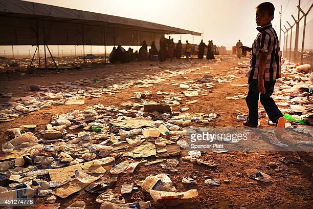 An Iraqi child walks over discarded water bottles at a registration area at a temporary displacement camp for Iraqis caughtup in the fighting in and...