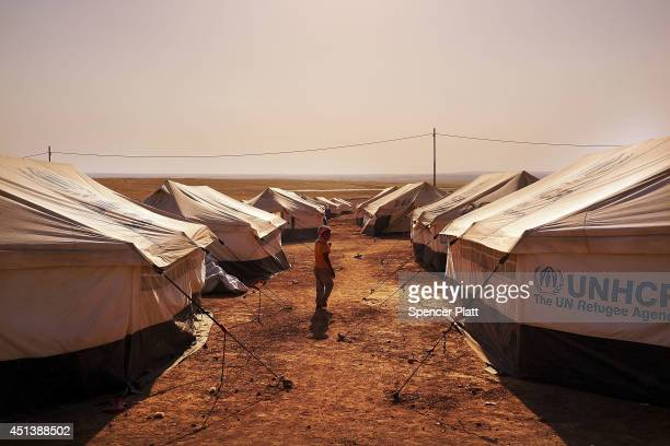 An Iraqi child walks through a displacement camp for those caughtup in the fighting in and around the city of Mosul on June 28 2014 in Khazair Iraq...