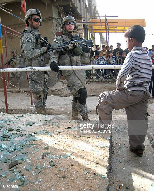 An Iraqi child watches US soldiers standing outside a bridle shop close to the scene of a road side bomb which damaged a mini bus carrying Shiite...