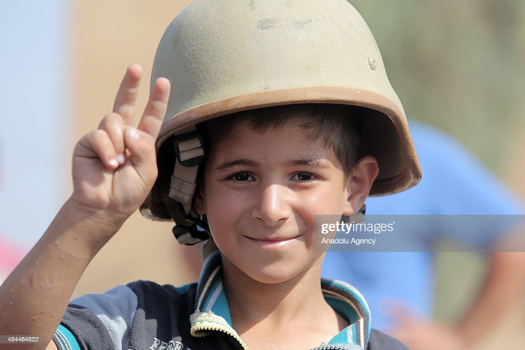 An Iraqi child wearing soldier helmet makes victory sign after Iraqi forces have freed the northern town of Amirli which had been under the siege of Islamic State militants for over two months in Saladin ,Iraq on September 1, 2014. Supported by Kurdish forces and Shiite militias, the Iraqi army launched an offensive shortly after the U.S. carried out airstrikes against Islamic State (IS) positions near the town, and dropped aid for the nearly 20,000 Shiite Turkmen trapped in Amirli. The government forces and Kurdish peshmerga forces have been fighting against the militant group to block their advance.