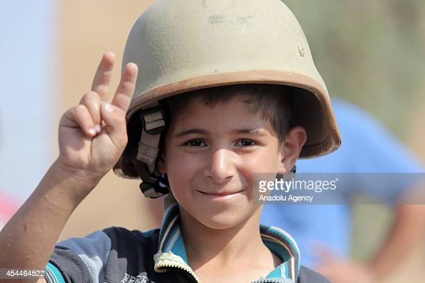 An Iraqi child wearing soldier helmet makes victory sign after Iraqi forces have freed the northern town of Amirli which had been under the siege of...