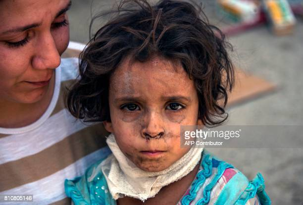 An Iraqi child who fled the fighting between government forces and Islamic State group jihadists in the Old City of Mosul sits with a woman as her...
