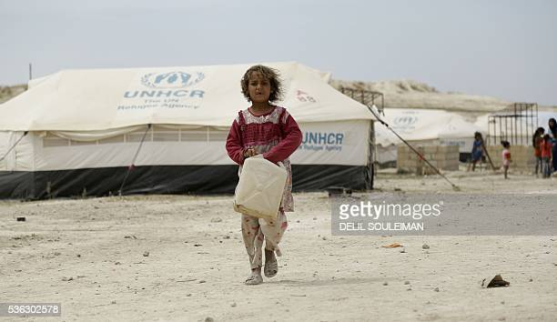 An Iraqi child who fled with her family the northern province of Nineveh following the advance of jihadists of the Islamic State group carries a...