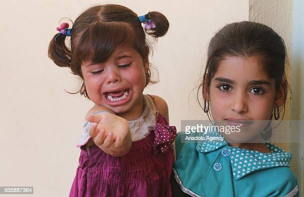 An Iraqi children holds a crying baby as Iraqi people in Fallujah town leave their home due to conflicts between Daesh and security forces in Anbar,...