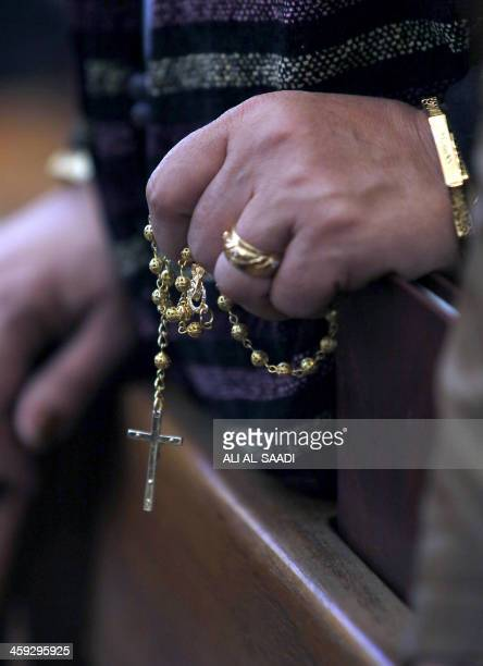 An Iraqi Christian holds a rosary during a Christmas mass at the Virgin Mary Chaldean church in the Karrada neighborhood of the capital Baghdad on...