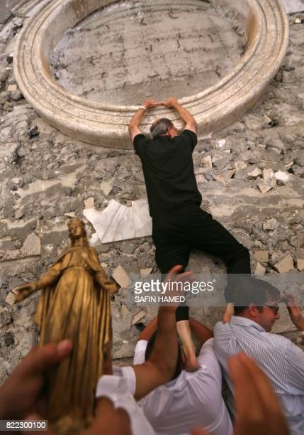 An Iraqi Christian man carries Lyon's Archbishop Cardinal Philippe Barbarin on his shoulders as the clergyman puts up a statue of Virgin Mary on the...