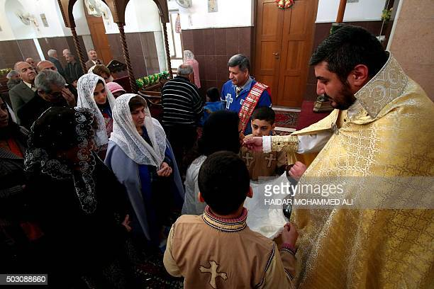 An Iraqi Christian priest gives the Eucharist during a mass at the Chaldean church in the southern city of Basra on January 1 2016 AFP PHOTO / HAIDAR...