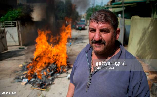 An Iraqi Christian stands by a fire burning garbage outside his house following his return to his hometown in the predominantly Christian Iraqi town...