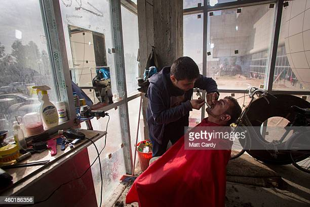 An Iraqi Christian who fled from his home because of Islamic State's advance earlier this year operates a barber shop inside the entrance hall of the...