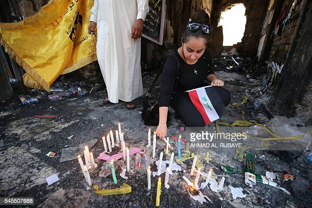 An Iraqi Christian woman lights a candle on July 8 2016 at the site of a suicide bombing that ripped through Baghdad's busy shopping district of...