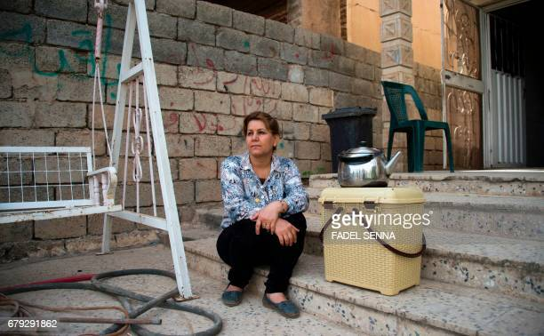 An Iraqi Christian woman sits by a kettle on a basket in front of a wall bearing graffiti left by Islamic State group fighters reading in Arabic 'The...