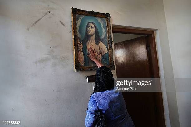 An Iraqi Christian woman touches a picture of Jesus before a Sunday service at St Joseph Chaldean Church on July 24 2011 in Baghdad Iraq Forming one...