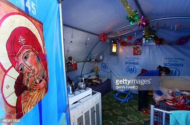 An Iraqi Christian woman who fled the violence in the northern Iraqi city of Mosul tends to her baby in a tent bearing an image of the virgin Mary...