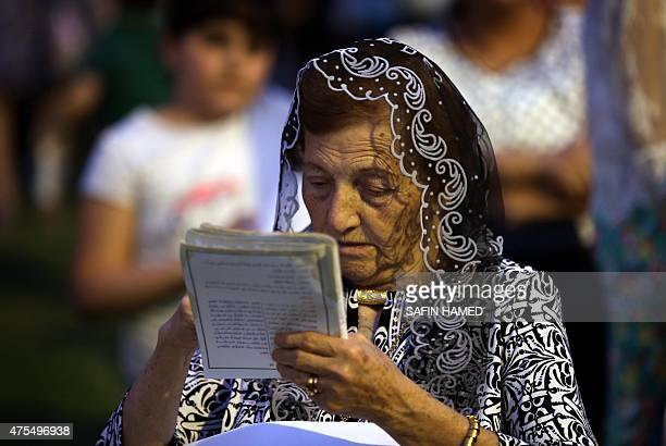 An Iraqi Christian woman who fled the violence in the northern Iraqi city of Mosul attends a mass celebrating the coronation of the Virgin Mary on...