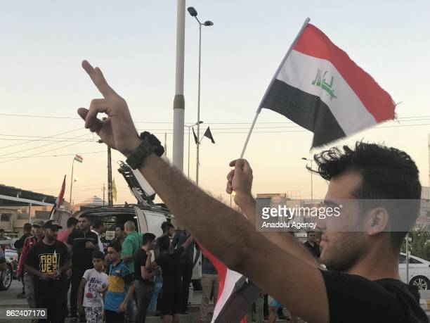 An Iraqi citizen gestures as he waves a Iraqi flag at Governorship Street after Iraqi government forces take the control of the city center from...