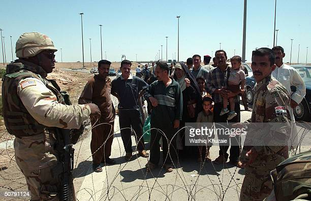 An Iraqi Civil Defense Corps member and a US Army soldier stand guard during a celebration May 1 2004 at a checkpoint on the outskirts of the...