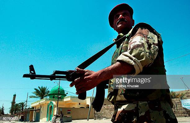 An Iraqi Civil Defense Corps member guards a street corner May 1 2004 in the flashpoint city of Fallujah Iraq An 1100 member Iraqi security force has...