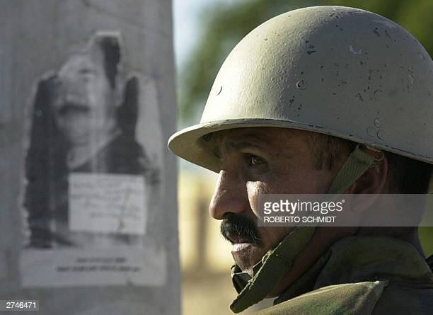STORY 'IRAQUSDEFENSE' An Iraqi Civil Defense Corps trainee keeps guard next to an antiUS proSaddam Hussein poster at a checkpoint in Tikrit during a...