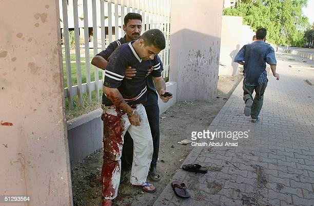 An Iraqi civilian helps severley injured journalist for AlArabiya TV station Mezan alTumeizi shortly before he died of his wounds on September 12...