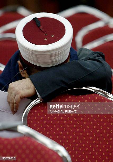An Iraqi cleric leans on a chair as he attends a conference organised by Muslim Scholars Union at a hotel in Baghdad 03 February 2008 More than 200...