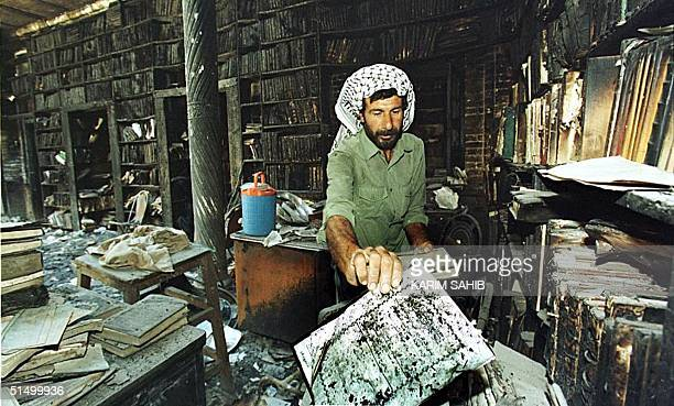 An Iraqi collect the remains of burned books 29 August 1999 at one of Baghdad's main library that caught fire 23 August 1999. Tens of thousands of...