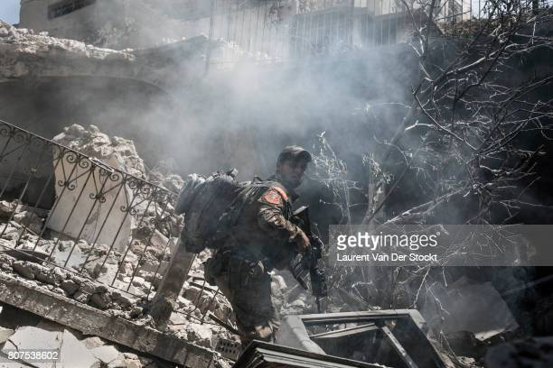 An Iraqi commando advances through the dust and rubble of alNuri mosque complex in Mosque complex on June 29 2017 in Mosul Iraq The Iraqi Army...