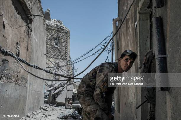 An Iraqi commando walks past the base of the ruined Hadba minaret of alNuri mosque complex on June 29 2017 The Iraqi Army Special Operations Forces...