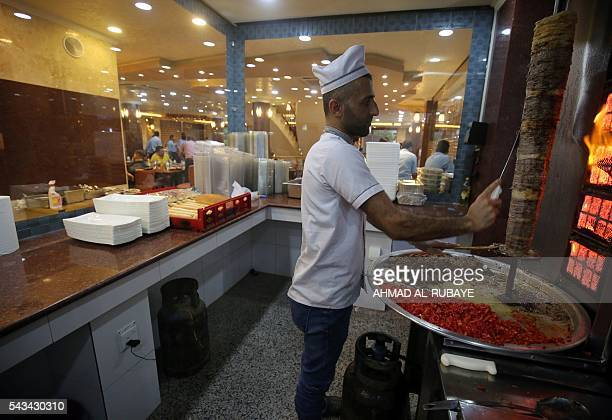 An Iraqi cook cuts shawarma meat at a restaurant where customers come to break their fast with the traditional Iftar meal during the Muslim fasting...
