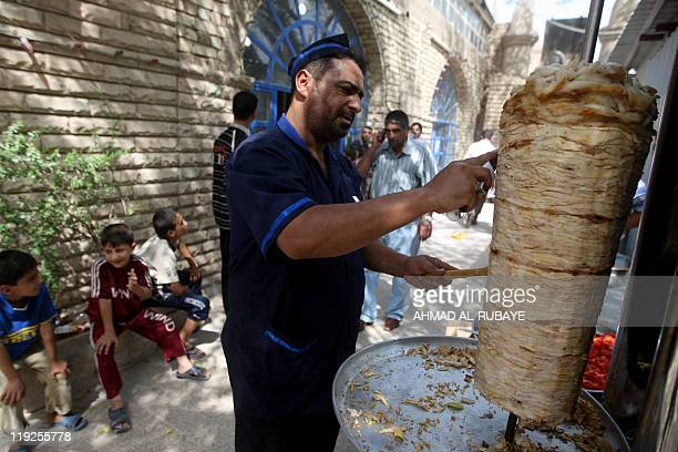 An Iraqi cook slices chicken to make shawarma sandwiches to be distributed in Baghdad's impoverished district of Sadr city on July 15 2011 at the...