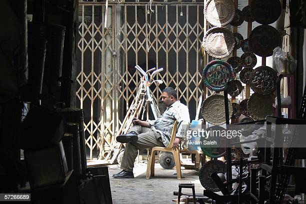 An Iraqi copper craftsman rests outside his shop at the copper market April 6 2006 in Baghdad Iraq According to the US Military Muhammed Hila Hammad...