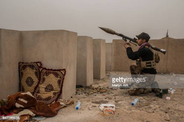 An Iraqi Counter Terrorism Service officer of the Golden Division aims an RPG at an Islamic State sniper position in the west Mosul district of...