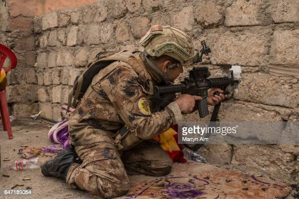 An Iraqi Counter Terrorism Service officer of the Golden Division aims at an Islamic State sniper position in the west Mosul district of alMamoun...