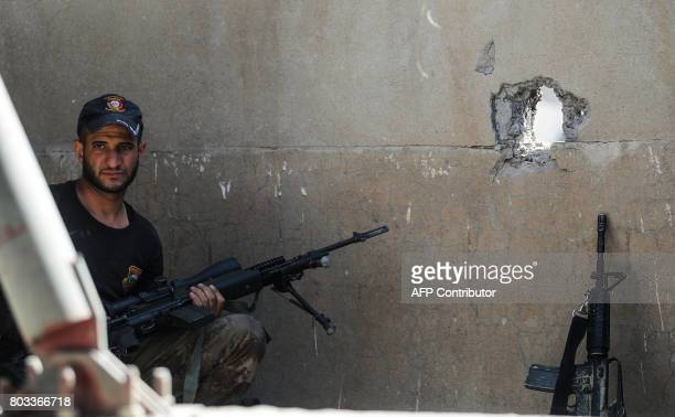 An Iraqi CounterTerrorism Service sniper looks on during the advance towards the Grand Mosque of Nuri in the Old City of Mosul on June 29 as the...