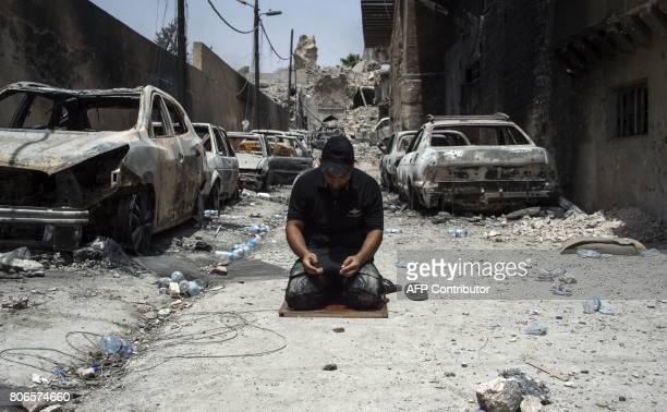 TOPSHOT An Iraqi CounterTerrorism Services member prays in the Old City of Mosul on July 3 2017 during an ongoing offensive to retake the city from...